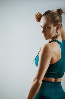 Femme athlétique avec des haltères en mains sur fond gris, bannière de remise en forme, motivation de remise en forme. photo d'un modèle de fitness musculaire travaillant avec des haltères sur fond gris.