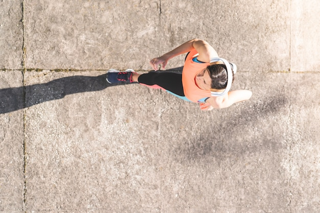Femme athlétique jogging sur le trottoir.