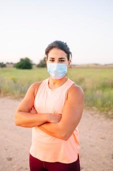 Femme athlétique avec masque facial marchant dans la rue