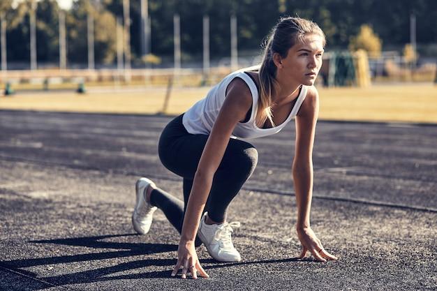 Femme athlétique sur piste commençant à courir.