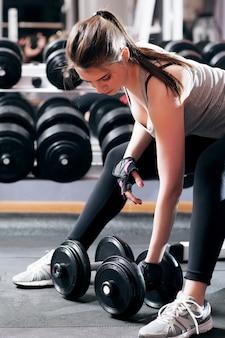 Femme athlétique pompage des muscles dans la salle de sport