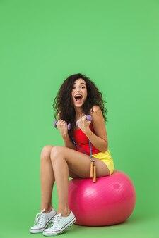 Femme athlétique portant des vêtements d'été soulevant des haltères alors qu'elle était assise sur un ballon de fitness pendant l'aérobic contre le mur vert