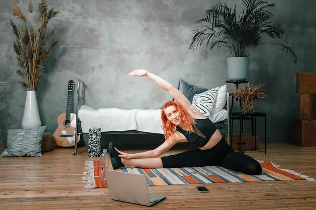 Femme athlétique positive aux cheveux rouges et vêtements de sport serrés qui s'étire à la maison.