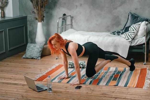 Femme athlétique positive aux cheveux roux et vêtements de sport serrés se déchaîne à la maison.