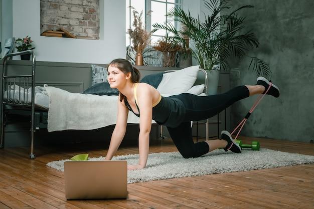 Femme athlétique positive avec des cheveux bien attachés et des vêtements de sport serrés effectuant des coups de pied allongés