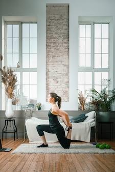 Femme athlétique positive avec des cheveux bien attachés et des vêtements de sport serrés qui s'étirent à la maison.