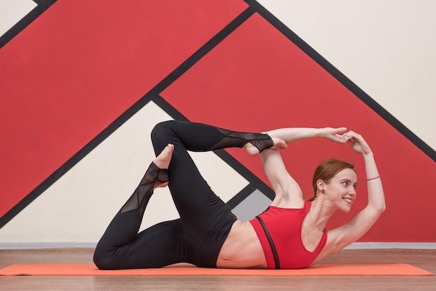 Femme athlétique pratiquant des exercices de yoga sains à l'intérieur