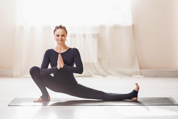 Femme athlétique pratiquant le yoga faisant l'exercice de flexion du genou vers l'avant janu shirshasana pose