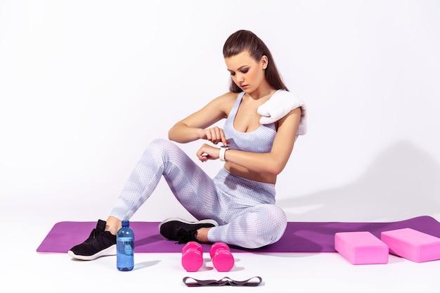 Femme athlétique regardant smartwatch et vérifiant les résultats de l'entraînement assis sur un tapis de yoga en caoutchouc