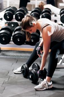 Femme athlétique s'entraînant avec des haltères