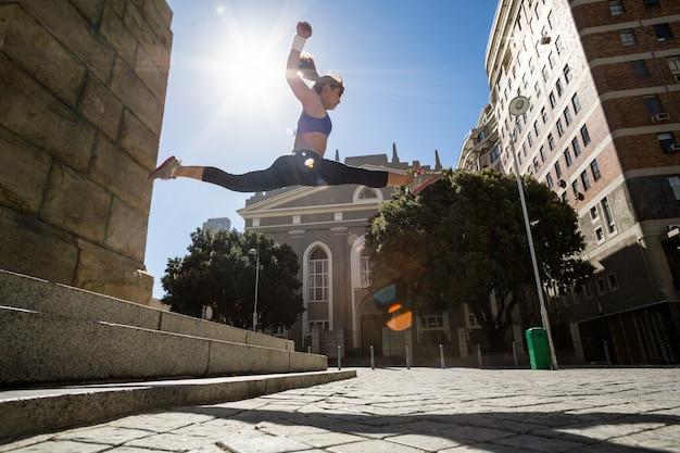 Femme athlétique sautant des escaliers et se fendant en l'air