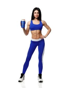 Femme athlétique avec un shaker sur fond blanc