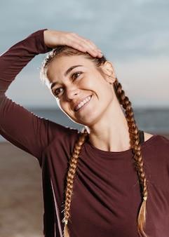 Femme athlétique smiley qui s'étend au bord de la plage
