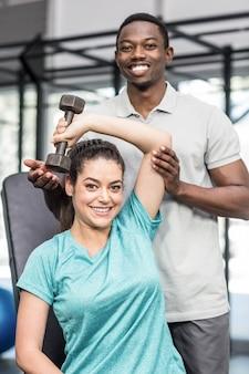 Femme athlétique, soulever des poids, aidée par un entraîneur au gymnase