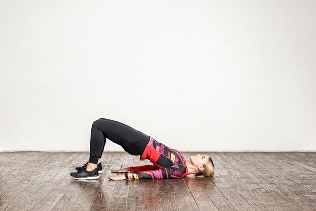 Femme athlétique en vêtements de sport serrés pratiquant le yoga, faisant une pose de pont en se penchant en arrière, étirant le corps, s'entraînant flexibilité, force musculaire. soins de santé et activité sportive à domicile. prise de vue en studio intérieur