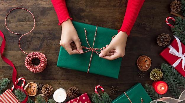 Femme attachant une boîte-cadeau au centre de noël, articles de décoration sur une table en bois