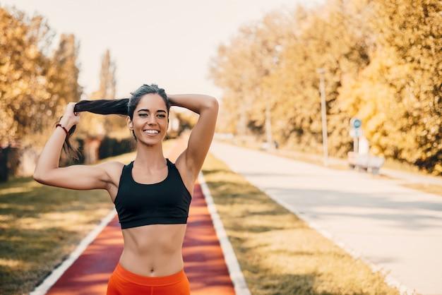 Femme attachant les cheveux en queue de cheval se prépare pour la course.