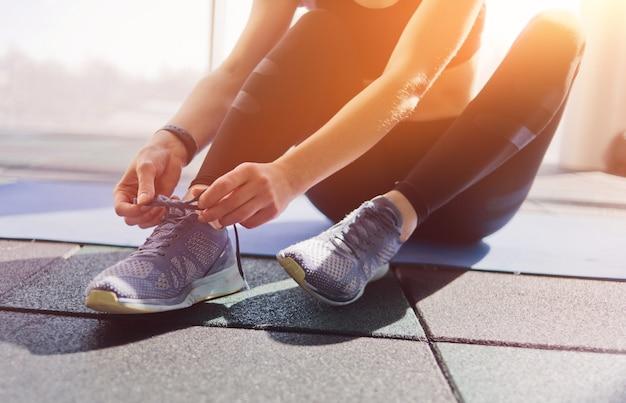 Femme attachant les lacets de baskets de sport assis sur un tapis dans la salle de sport