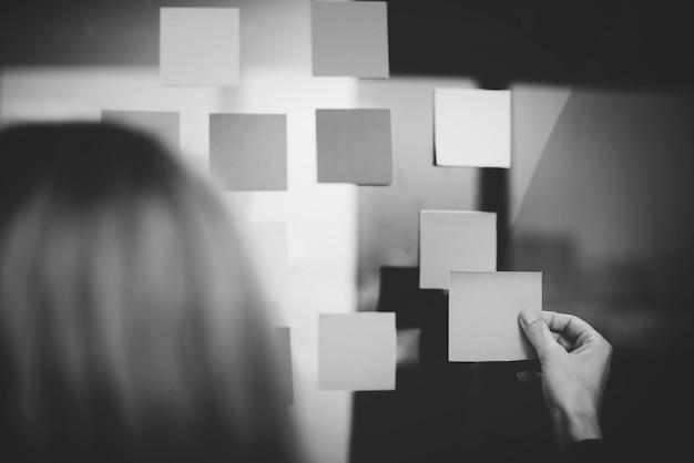 Femme attachant une note à un tableau