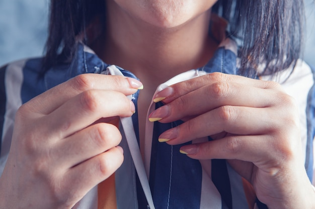 La femme attache le bouton de la chemise