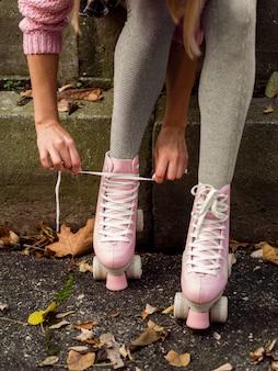 Femme, attacher, lacets, sur, patins a roulettes