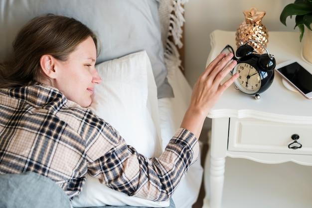 Femme atteignant la main pour éteindre l'alarme