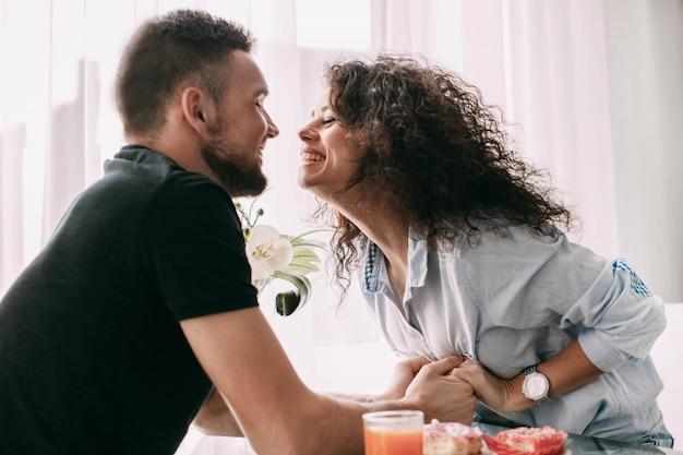 La femme atteint son homme pour un bisou assis à la table à manger