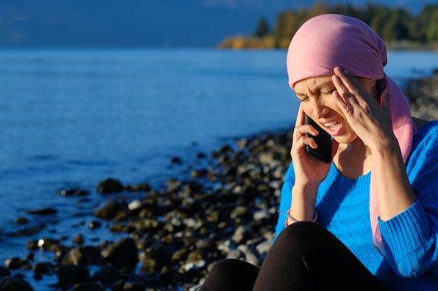 Femme atteinte de cancer, parler sur son téléphone portable avec un mal de tête tenant sa tête