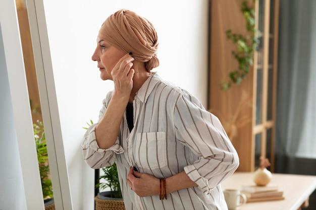 Femme atteinte d'un cancer de la peau se regardant dans le miroir