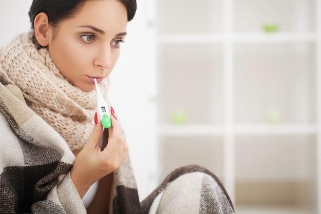 Femme atteinte du virus de la grippe, couchée dans son lit, elle mesure sa température avec un thermomètre et se touche le front