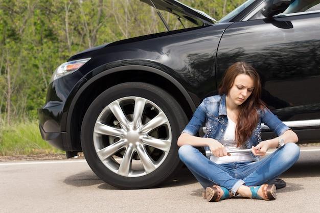 Femme attendant à côté de sa voiture en panne