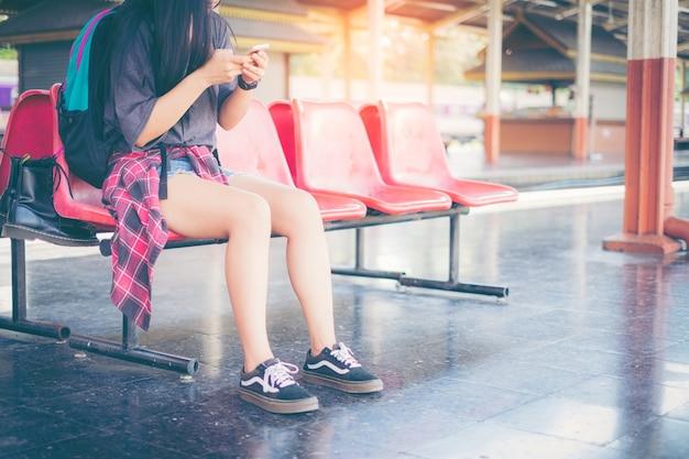 Femme attendant sur la plate-forme de la gare avec sac à dos en utilisant un téléphone intelligent.
