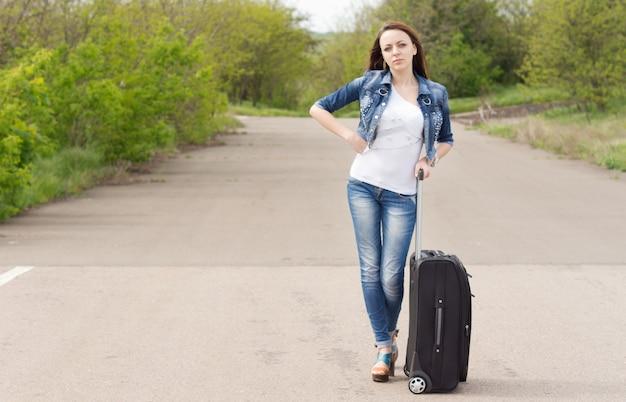 Femme attendant sur la route avec sa valise