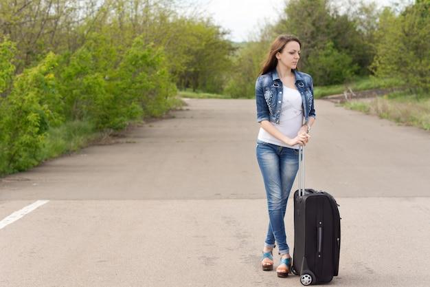 Femme attendant avec sa valise sur la route