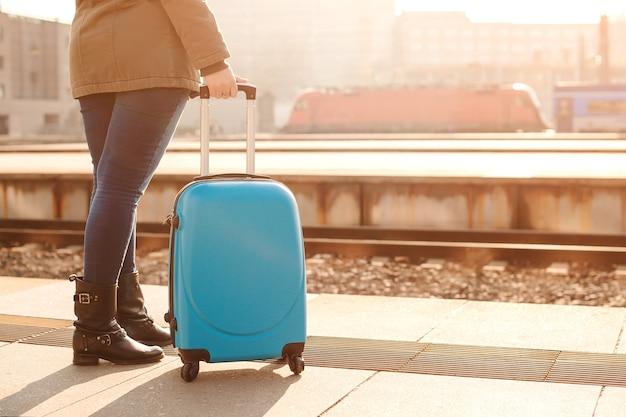 Femme attendant un train à la gare le matin. voyage en train.