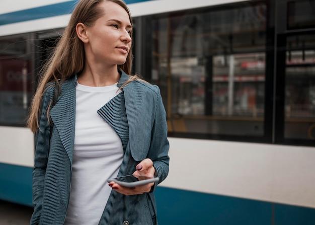 Femme en attente de la vue basse de bus
