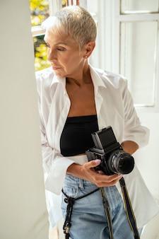 Femme attentive regardant la fenêtre et créant des idées de prise de vue
