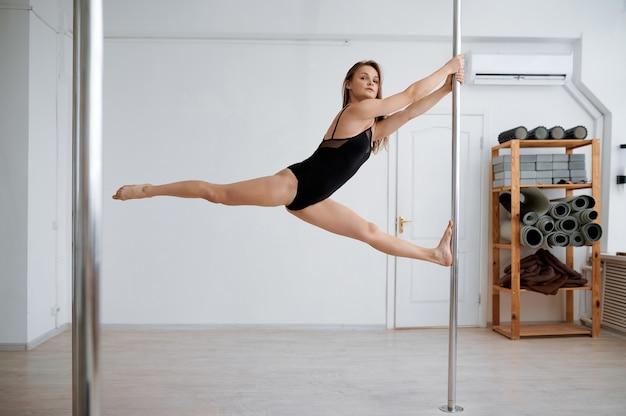 Femme attirante sur la formation de pole dance en classe. danseuses professionnelles exerçant dans une salle de sport, pole-dance