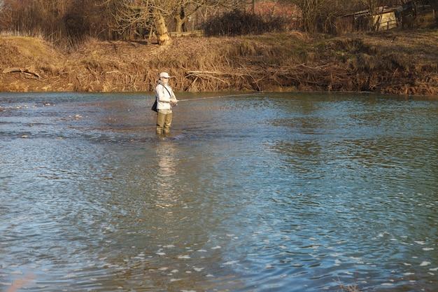 Femme attrape des poissons en train de filer debout dans une rivière