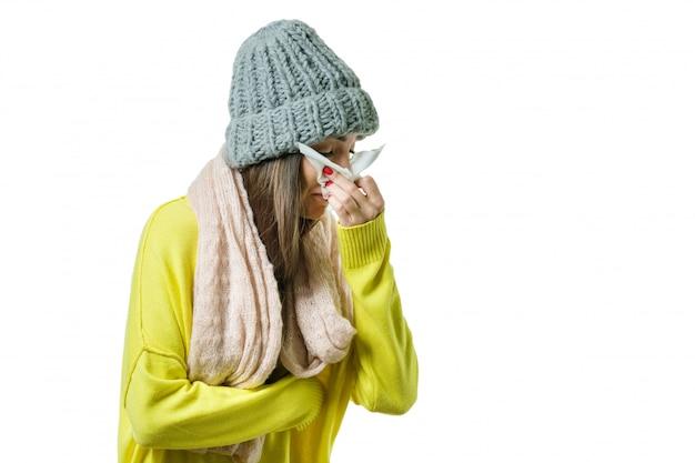 Femme attrapée un rhume dans un bonnet chaud et une écharpe avec un mouchoir