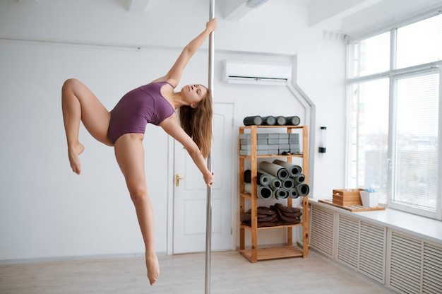 Femme attrayante sur l'entraînement de pole dance en classe. danseuses professionnelles exerçant dans une salle de sport, pole-dance