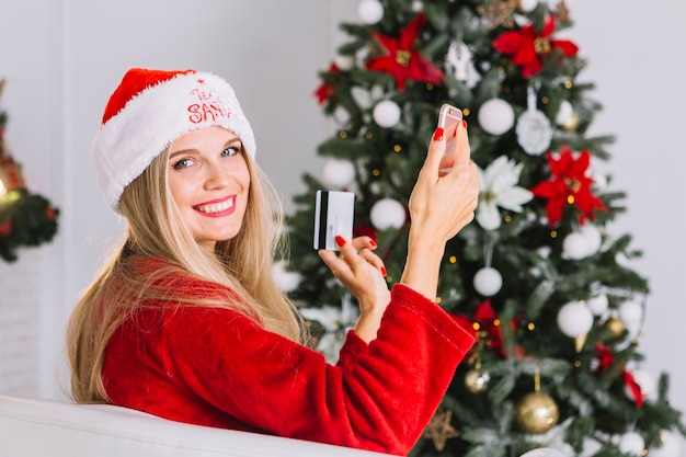 Femme au bonnet de noel assis avec téléphone