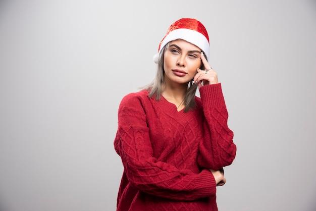 Femme au bonnet de noel pensant sur fond gris.