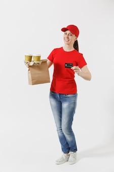 Femme au bonnet rouge, t-shirt donnant une commande de restauration rapide isolé sur fond blanc. courrier féminin tenant une carte de crédit, un paquet de papier avec de la nourriture, du café. livraison de produits du magasin ou du restaurant à domicile.