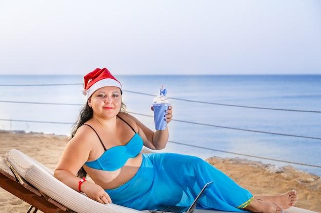 Une femme au bord de la mer dans une chaise longue en maillot de bain et un chapeau de père noël boit un cocktail.
