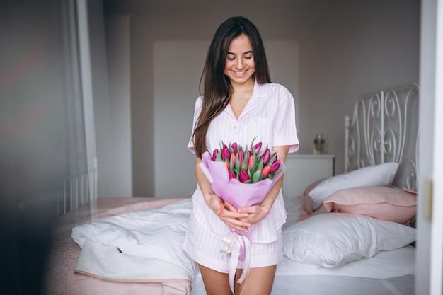 Femme au bouquet de fleurs dans la chambre