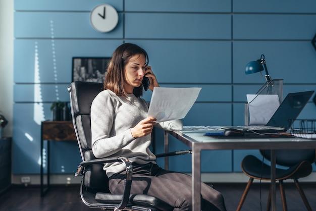 Femme au bureau parlant au téléphone portable tenant un document travaillant sur son lieu de travail.