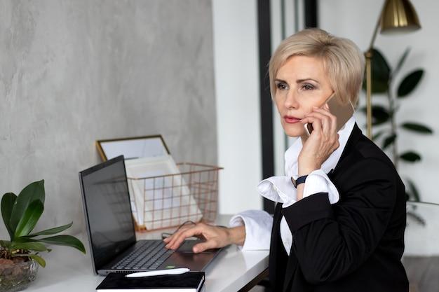 Femme au bureau parlant au téléphone