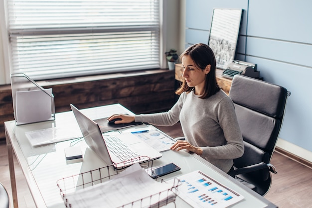 Une femme au bureau travaille avec un ordinateur portable, regarde l'écran.