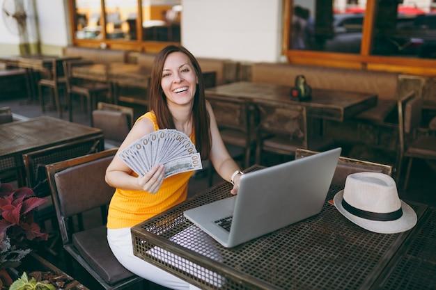 Femme au café de la rue en plein air assis avec un ordinateur portable moderne, tient dans la main un tas de billets de banque en dollars